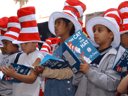"Children read from ""The Cat in the Hat"" book at a ceremony honoring the late children's book author Dr. Seuss (Theodore Geisel) with a star on the Hollywood Walk of Fame on March 11, 2004 in Hollywood , California. (Photo by Vince Bucci/Getty Images)"