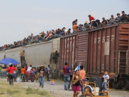 Central American immigrant get on the so-called La Bestia (The Beast) cargo train, in an attempt to reach the Mexico-US border, in Arriaga, Chiapas state, Mexico on July 16, 2014. AFP PHOTO/ELIZABETH RUIZ (Photo by ELIZABETH RUIZ / AFP) (Photo credit should read ELIZABETH RUIZ/AFP via Getty Images)