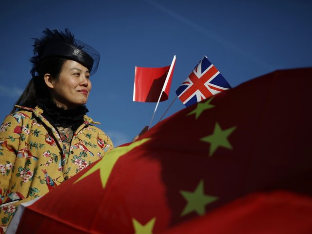 BARKING, ENGLAND - JANUARY 18: A woman holds a Union flag and a Chinese Flag as a train engine pulls carriages that started their Journey in Yiwu in China into Barking rail freight terminal on January 18, 2017 in Barking, England. After travelling for 16 days and covering around 7,456 …