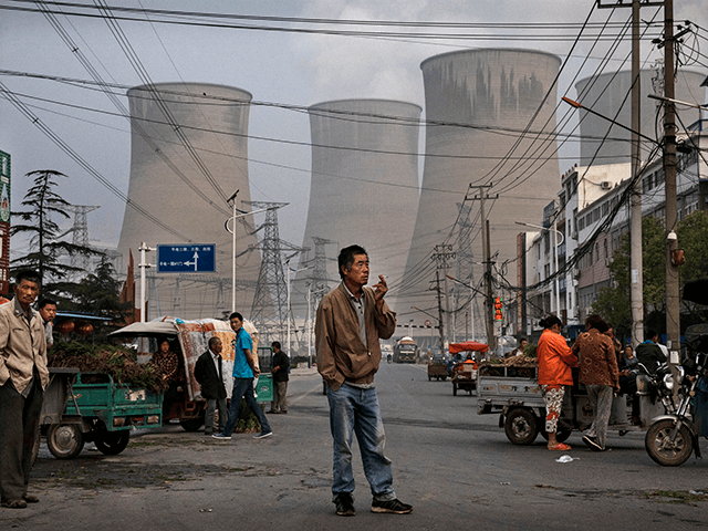 Chinese street vendors and customers gather at a local market outside a state owned Coal fired power plant near the site of a large floating solar farm project under construction by the Sungrow Power Supply Company on a lake caused by a collapsed and flooded coal mine on June 14, …