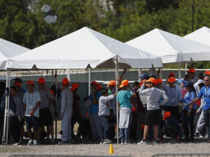In this Monday, May 6, 2019 file photo, migrant children stand outside the Homestead Temporary Shelter for Unaccompanied Children in Homestead, Fla. The U.S. government is providing long-distance video counseling to teens housed at the country's largest migrant detention center as officials struggle to accommodate increasing numbers of minors illegally …