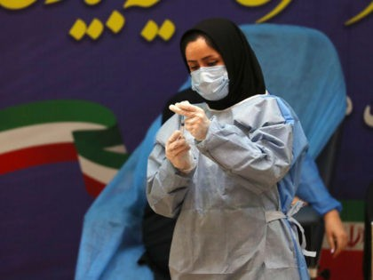 An Iranian health worker prepares a dose of the COVID-19 vaccine as the country launches its inoculation campain, at the Imam Khomeini hospital in the capital Tehran, on February, 9, 2021. - The inoculation effort for 80-million-plus population is starting with Russia's Sputnik V vaccine, authorities have said, as the …