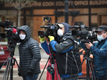 In this file photo, Journalist wearing masks document a protest where demonstrators were calling on the governor to suspend rent and mortgage payments to help those who have lost their income due to the coronavirus on April 30, 2020 in Chicago, Illinois. On May 1, the state of Illinois will …