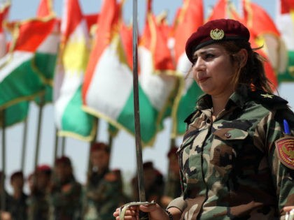 A woman fighter of the Iraqi Kurdish Peshmerga attends a ceremonial line-up past flying flags of Iraq's autonomous Kurdistan region, during a training session by German military officers during the German Defence Minister's visit at a facility on the outskirts of Arbil, the capital of the autonomous region, on August …