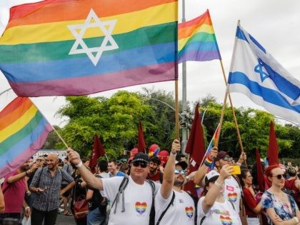 Participants wave gay rainbow pride flags during the 18th annual Jerusalem Gay Pride parade on June 06, 2019. - Thousands were expected to participate in Jerusalem's annual Gay Pride march Thursday under high security following a knife attack by a Jewish religious extremist that killed a teenager in 2015. Police …