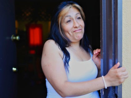 Maria Gonzalez, 38, peeks through her door as she is questioned about the upcoming US Census at her home in Long Beach, Calif., Aug. 24, 2009. For the first time, the decennial census will be distributed in the two languages to 13.5 million households in predominantly Spanish-speaking neighborhoods. Latino advocates …