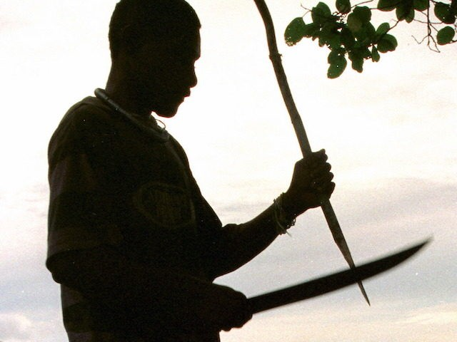 In this file photo, a Guadalcanal guard sharpens a stake with his machette near the abandoned village of Vilu, Solomon Islands 20 June 1999 after the area was cleared of Malaitans by the Guadalcanal Liberation Army. (Torsten Blackwood/AFP via Getty Images)