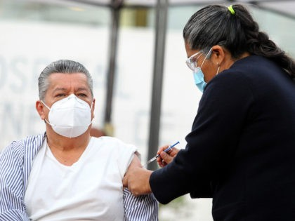 A nurse administrates a Pfizer-BioNTech Covid-19 vaccine to 66-years-old epidemiological doctor David Diaz Santana, during the start of vaccination against the SARS-CoV-2 virus to medical personnel of the General Hospital of the West Zoquipan in Zapopan, Jalisco state, Mexico, on January 13, 2021. (Ulises Ruiz/AFP via Getty Images)
