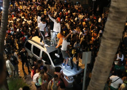 People gather while exiting the area as an 8pm curfew goes into effect on March 21, 2021 in Miami Beach, Florida. College students have arrived in the South Florida area for the annual spring break ritual, prompting city officials to impose an 8pm to 6am curfew as the coronavirus pandemic …
