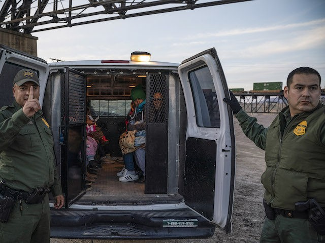 In this file photo, a group of about 30 Brazilian migrants, who had just crossed the border, get into a US Border Patrol van, taking them off the property of Jeff Allen, who used to run a brick factory near Mt. Christo Rey on the US-Mexico border in Sunland Park, …