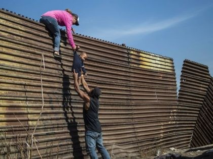 In this file photo, a group of Central American migrants climb the border fence between Mexico and the United States, near El Chaparral border crossing, in Tijuana, Baja California State, Mexico, on November 25, 2018. (Pedro Pardo/AFP via Getty Images)