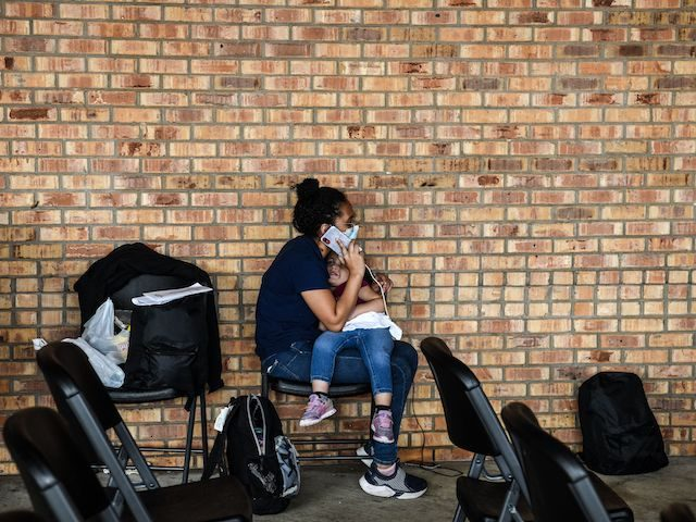 A migrant girl from Central America waits with her mother for a bus after they are dropped off by the US Customs and Border Protection at a bus station near the Gateway International Bridge, between the cities of Brownsville, Texas, and Matamoros, Mexico, on March 15, 2021 in Brownsville, Texas. …