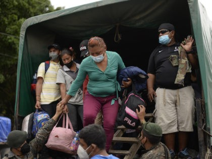 Honduran migrants who voluntarely return to Honduras are helped by soldiers as they get off an army truck in El Florido, Chiquimula, Guatemala on January 19, 2021. - On buses and trucks, Guatemala transported Tuesday several groups of migrants who were part of a US-bound caravan back to Honduras, after …