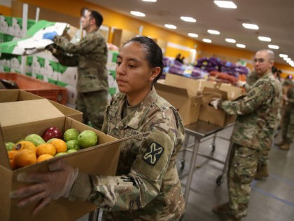 In this file photo, members of the California National Guard 115th Regional Support Group help pack boxes of fruit and other food at the Second Harvest Food Bank of Silicon Valley on March 24, 2020 in San Jose, California. (Justin Sullivan/Getty Images)