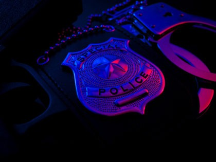 Police raid at night and you are under arrest concept with a police badge, gun and a pair of handcuffs at night illuminated by the flashing red and blue police lights
