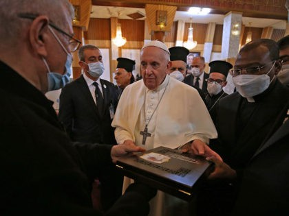 Pope Francis receives a gift during his visit to the Syro-Catholic Cathedral of Our Lady of Salvation (Sayidat al-Najat) in the capital Baghdad at the start of the first ever papal visit to Iraq on March 5, 2021. - In an address to the faithful in Baghdad, Pope Francis expressed …