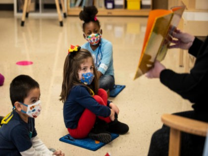 Pre-kindergarten students listen as their teacher reads a story at Dawes Elementary in Chicago, Monday, Jan. 11, 2021. Chicago Public Schools students began their return to the classroom Monday as school doors opened to thousands of pre-kindergarten and some special education students after going remote last March due to the …