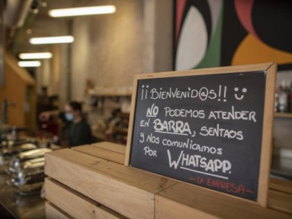 "A banner reading in Spanish: ""Welcome, we cannot serve in the bar. Sit down and we communicate by WhatsApp"" is pictured at La Francachela restaurant in Madrid, Spain, Friday, March 26, 2021. Experimenting with cutting back one workday per week is about to go nationwide in Spain. A 3-year pilot …"