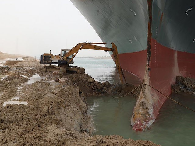This photo released by the Suez Canal Authority on Thursday, March 25, 2021, shows a backhoe trying to dig out the keel of the Ever Given, a Panama-flagged cargo ship, that is wedged across the Suez Canal and blocking traffic in the vital waterway. An operation is underway to try …