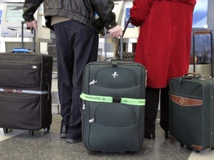 In this file photo, travelers with their luggage are seen in Terminal 3 February 21, 2006 at O'Hare International Airport in Chicago, Illinois. (Tim Boyle/Getty Images)