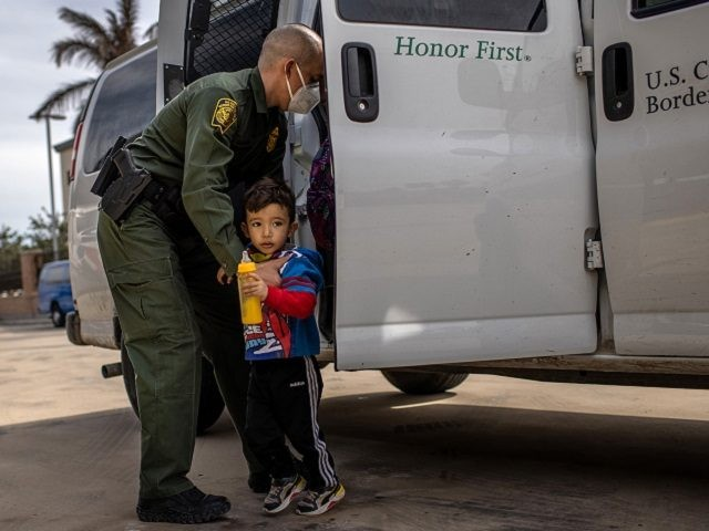 BROWNSVILLE, TEXAS - FEBRUARY 26: A U.S. Border Patrol agent delivers a young asylum seeker and his family to a bus station on February 26, 2021 in Brownsville, Texas. U.S. immigration authorities are now releasing many asylum seeking families after detaining them while crossing the U.S.-Mexico border. The immigrant families …
