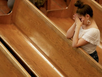 A woman bows her head in St Pius X Church at a vigil for victims after a mass shooting which left at least 20 people dead on August 3, 2019 in El Paso, Texas. (Mario Tama/Getty Images