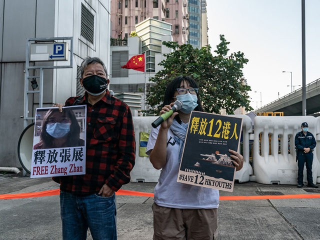 HONG KONG, CHINA - DECEMBER 28: Pro-democracy activists hold placards as they show support for twelve Hong Kong residents detained in mainland China and former lawyer Zhang Zhan outside the Liaison Office of the Central People's Government on December 28, 2020 in Hong Kong, China. The first day of trial …