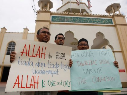 "Muslims hold placards up outside a mosque following Friday prayers in central Kuala Lumpur, Malaysia, Friday, Jan. 8, 2010. Three Malaysian churches were attacked with firebombs, causing extensive damage to one, as Muslim worshippers pledged Friday to prevent Christians from using the word ""Allah,"" escalating religious tensions in this multi-racial …"
