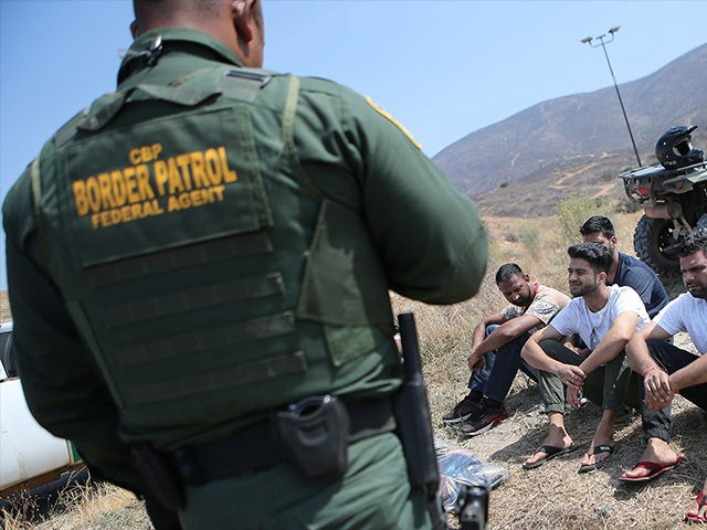 SAN DIEGO, CA - JULY 16: A U.S. Border Patrol agent monitors a group of apprehended males from India who illegally crossed the U.S.-Mexico border on July 16, 2018 in San Diego, California. The entire Southwest border saw 34,114 U.S. Border Patrol apprehensions in the month of June compared with …