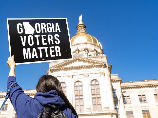 ATLANTA, GA - MARCH 03: Demonstrators stand outside of the Georgia Capitol building, to oppose the HB 531 bill on March 3, 2021 in Atlanta, Georgia. HB 531 will add controversial voting restrictions to the state's upcoming elections including restricting ballot drop boxes, requiring an ID requirement for absentee voting …