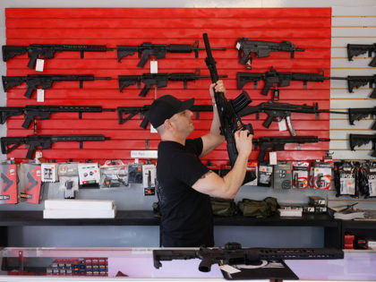 "DELRAY BEACH, FLORIDA - MARCH 24: Brandon Wexler helps a customer look at weapons at WEX Gunworks on March 24, 2021 in Delray Beach, Florida. U.S. President Joe Biden has called on lawmakers to ""immediately pass"" legislation to help curb gun violence in the county. (Photo by Joe Raedle/Getty Images)"