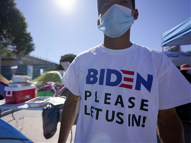 """A Honduran man seeking asylum in the United States wears a shirt that reads, """"Biden please let us in,"""" as he stands among tents that line an entrance to the border crossing, Monday, March 1, 2021, in Tijuana, Mexico. President Joe Biden is holding a virtual meeting with Mexican President …"""