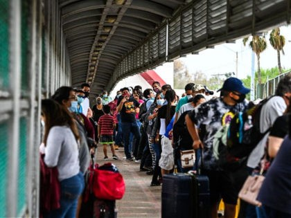 "Migrants mostly form Central America wait in line to cross the border at the Gateway International Bridge into the US from Matamoros, Mexico to Brownsville, Texas, on March 15, 2021. - It's the new normal for migrant families under President Joe Biden, after the harsh ""zero tolerance"" approach of Donald …"