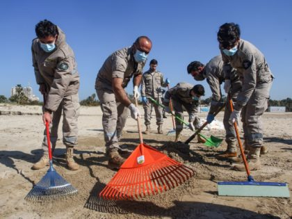 Volunteers from youth associations clean a contaminated beach in the southern Lebanese city of Tyre on February 27, 2021, following last week's offshore oil spill that drenched the northern Israeli coastline and reached parts of the neighbouring Lebanese beaches. (Photo by Mahmoud ZAYYAT / AFP) (Photo by MAHMOUD ZAYYAT/AFP via …