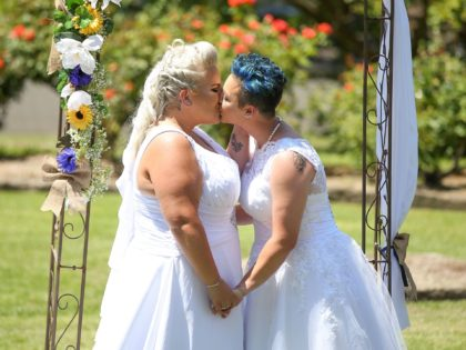 SYDNEY, AUSTRALIA - DECEMBER 16: Same-sex couple Amy Laker and Lauren Price kiss during their wedding ceremony on December 16, 2017 in Sydney, Australia. Lauren and Amy are the first gay couple to be legally married in Australia, after same-sex marriage was legalised on 9 December 2017. The women - …
