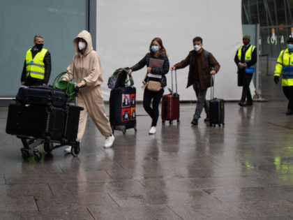 """LONDON, ENGLAND - FEBRUARY 15: Passengers arriving at Heathrow's Terminal 5 are escorted by security personal to buses on February 15, 2021 in London, England. From today, people arriving from 33 """"red list"""" countries, including South Africa and the United Arab Emirates, must isolate in hotels rooms for 10 days …"""