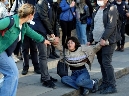 A woman reacts as riot police officers detain a student during a protest, in Ankara, Turkey, Friday, Feb. 5, 2021. Students and faculty members at Bogazici University have been staging demonstrations in protest of President Recep Tayyip Erdogan's Jan. 1 appointment of an academic with links to his ruling party, …