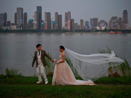 A couple poses during a wedding photo shoot by wedding photographer Zhang (not pictured), next to Yangtze River in Wuhan, in China's central Hubei province on May 16, 2020. - Authorities in the pandemic ground zero of Wuhan have ordered mass COVID-19 testing for all 11 million residents after a …