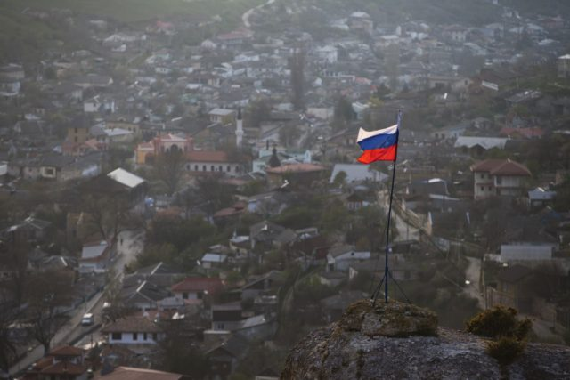 "In this March 28, 2014 file photo, a Russian national flag flies on a hilltop near the city of Bakhchysarai, Crimea. The Group of Seven major industrialized countries on Thursday March 18, 2021, issued a strong condemnation of what it called Russia's ongoing ""occupation"" of the Crimean Peninsula, seven years …"