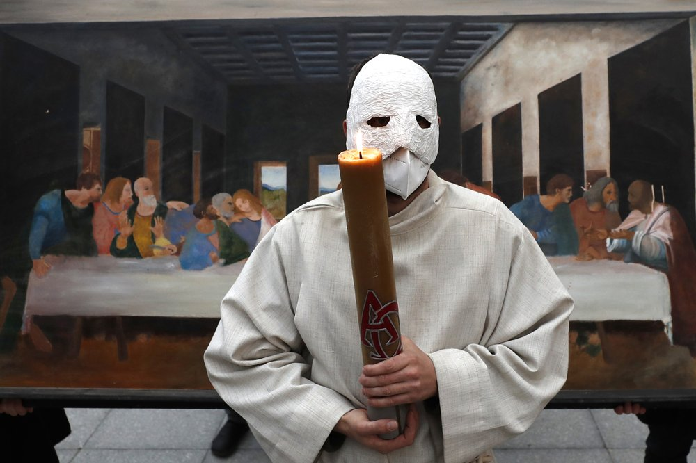 A participant wearing a mask holds a candle as he stands in front of a depiction of the painting the Last Supper during an Easter procession marching through the streets of Ceske Budejovice, Czech Republic, Thursday, April 1, 2021. (AP Photo/Petr David Josek)