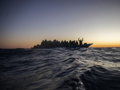 Migrants and refugees from different African nationalities wait for assistance on an overcrowded wooden boat, as aid workers of the Spanish NGO Open Arms approach them in the Mediterranean Sea, international waters, at 122 miles off the Libyan coast, Friday, Feb. 12, 2021. (AP Photo/Bruno Thevenin)