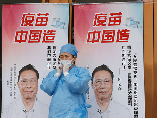 """A medical worker adjusts her mask near propaganda boards showing famed Chinese medical expert Zhong Nanshan and the words """"Vaccine China Made"""" outside vaccination center in Beijing Friday, April 9, 2021. In a rare admission of the weakness of Chinese coronavirus vaccines, the country's top disease control official says their …"""