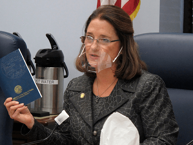 In this Jan. 27, 2021 file photo, Alaska state Sen. Lora Reinbold, an Eagle River Republican, holds a copy of the Alaska Constitution during a committee hearing in Juneau, Alaska. Alaska Airlines has banned the Alaska state senator for refusing to follow mask requirements. Last week Reinbold was recorded in …