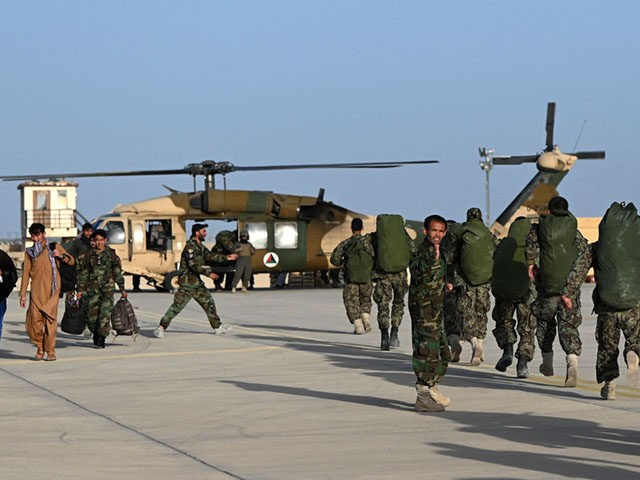 In this photograph taken on March 25, 2021 Afghan (ANA) soldiers walks towards an Afghan Air Force Black Bawk helicopter at the Shorab Military Camp in Lashkar Gah, in the Afghan province of Helmand. (Photo by WAKIL KOHSAR / AFP) (Photo by WAKIL KOHSAR/AFP via Getty Images)