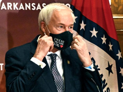 In this July 20, 2020 file photo, Arkansas Gov. Asa Hutchinson removes his mask before a briefing at the state capitol in Little Rock. Gov. Hutchinson on Monday, April 5, 2021 vetoed legislation that would have made his state the first to ban gender confirming treatments or surgery for transgender …