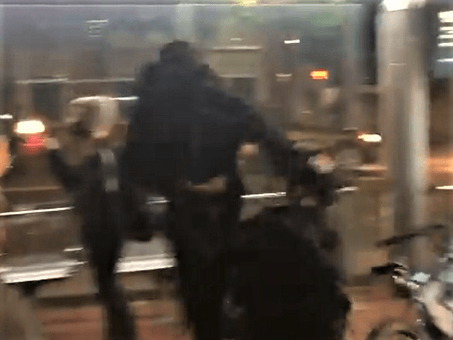 An Antifa rioter punches a police officer in the face on April 20. (Twitter Video Screencapture/The Oregonian)