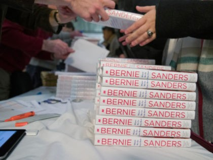 Attendees receive a copy of Sen. Bernie Sanders', I-Vt., new book, 'Where We Go From Here: Two Years in the Resistance', at a George Washington University/Politics and Prose event, Tuesday, Nov. 27, 2018, in Washington. (AP Photo/Alex Brandon)