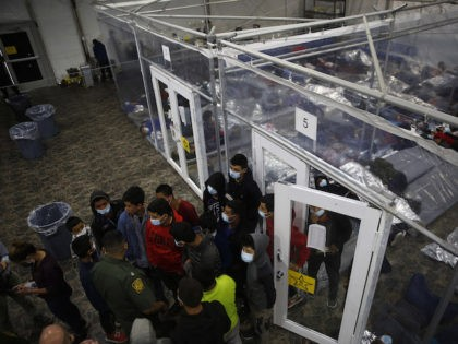 Young minors talk to an agent outside at a pod in the Donna Department of Homeland Security holding facility, the main detention center for unaccompanied children in the Rio Grande Valley run by the US Customs and Border Protection, (CBP), in Donna, Texas on March 30, 2021. - The minors …