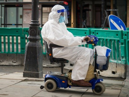 LONDON, UNITED KINGDOM - JULY 02: A person wearing a full protective suit and face mask travels along Regent Street in a mobility scooter on July 02, 2020 in London, United Kingdom. Many UK businesses are announcing job losses due to the effects of the Coronavirus Pandemic and Lockdown. (Photo …