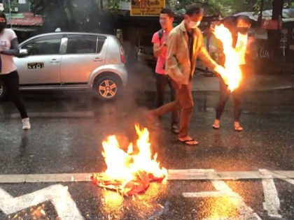 This screengrab provided via AFPTV video footage taken on April 5, 2021 shows protesters burning a Chinese national flag during a demonstration against Beijings support for the Myanmar military in Yangon. (Photo by - / AFPTV / AFP) (Photo by -/AFPTV/AFP via Getty Images)